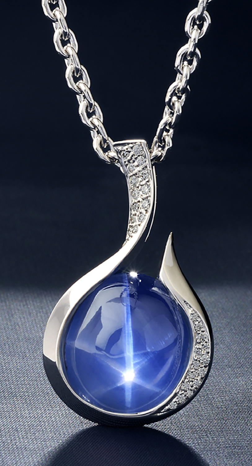 Large star sapphire with star in middle in silver and diamond pendant hanging from silver chain