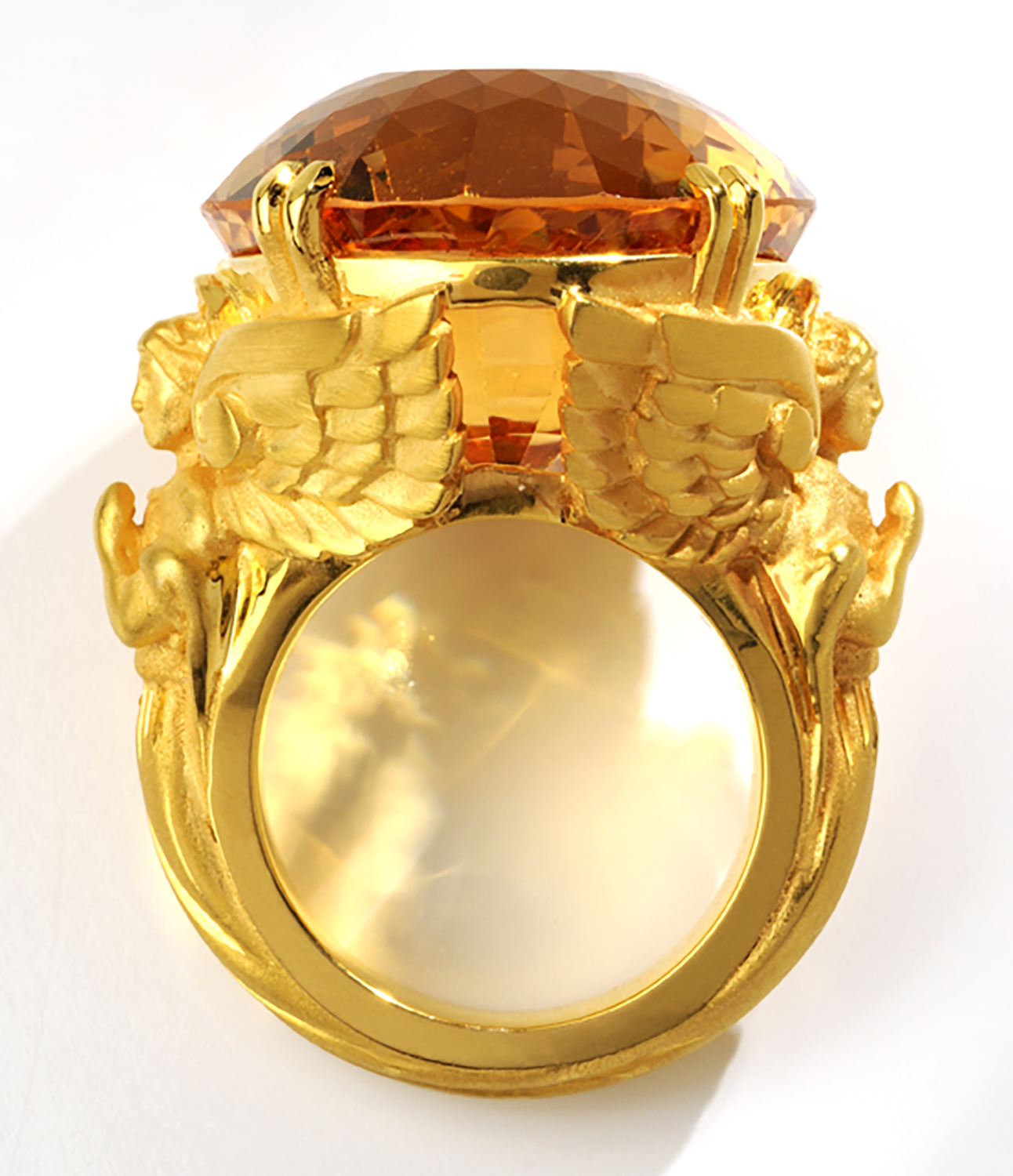 Large museum oval topaz mounted on heavy gold ring flanked by twin angel carvings on white background Product Photography