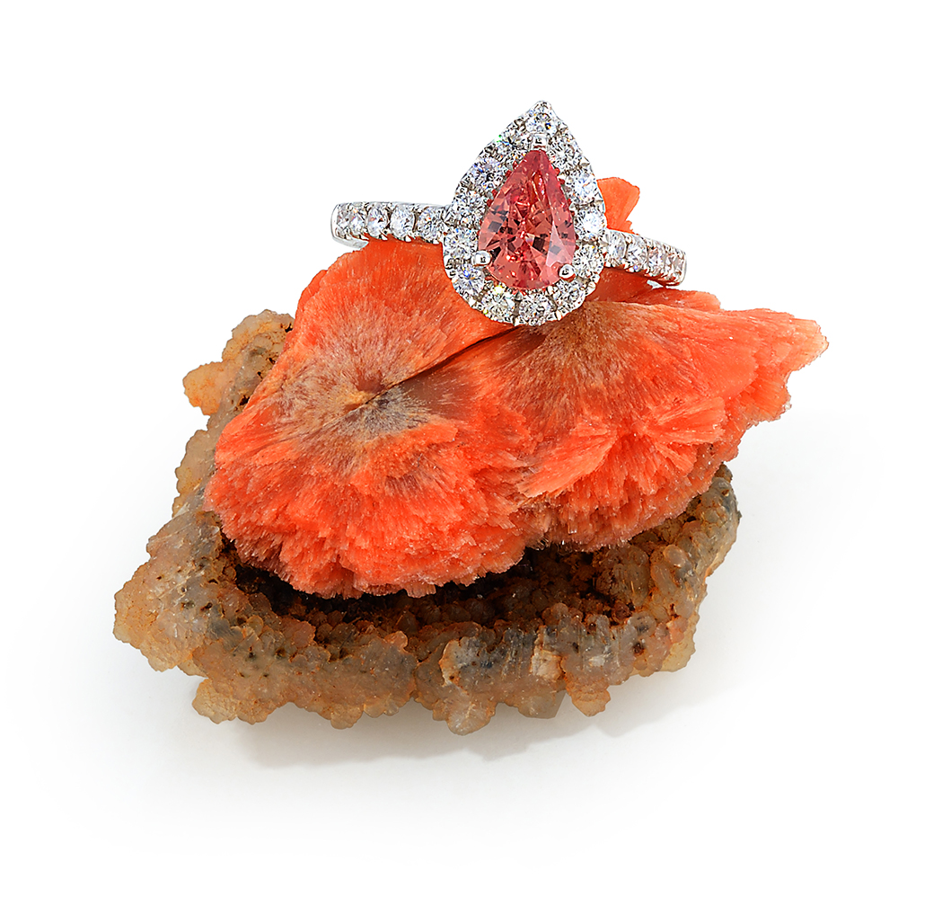 1.08ct padparadscha sapphire ring with .58ct total diamond weight and 18k white gold mounting on a very rare orange scolecite crystal on white background