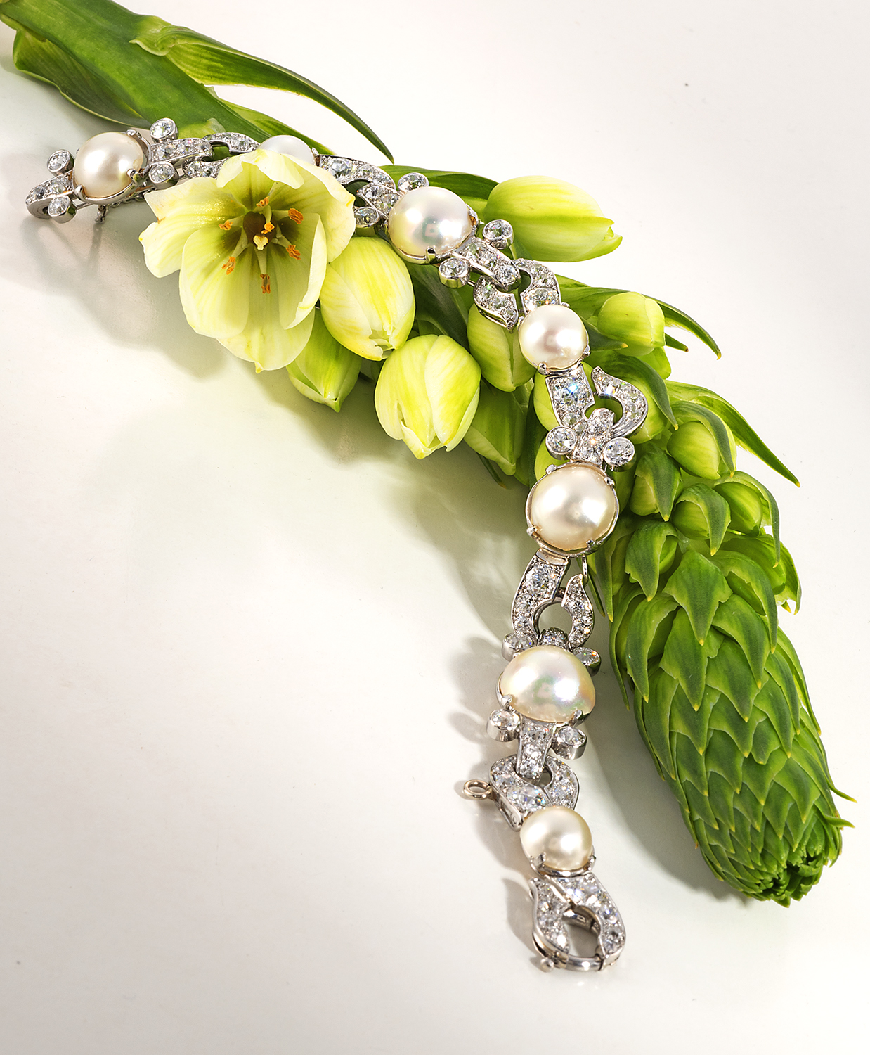 Beautiful vintage diamond and pearl bracelet arranged over a flower bud with delicate white flowers and green buds.