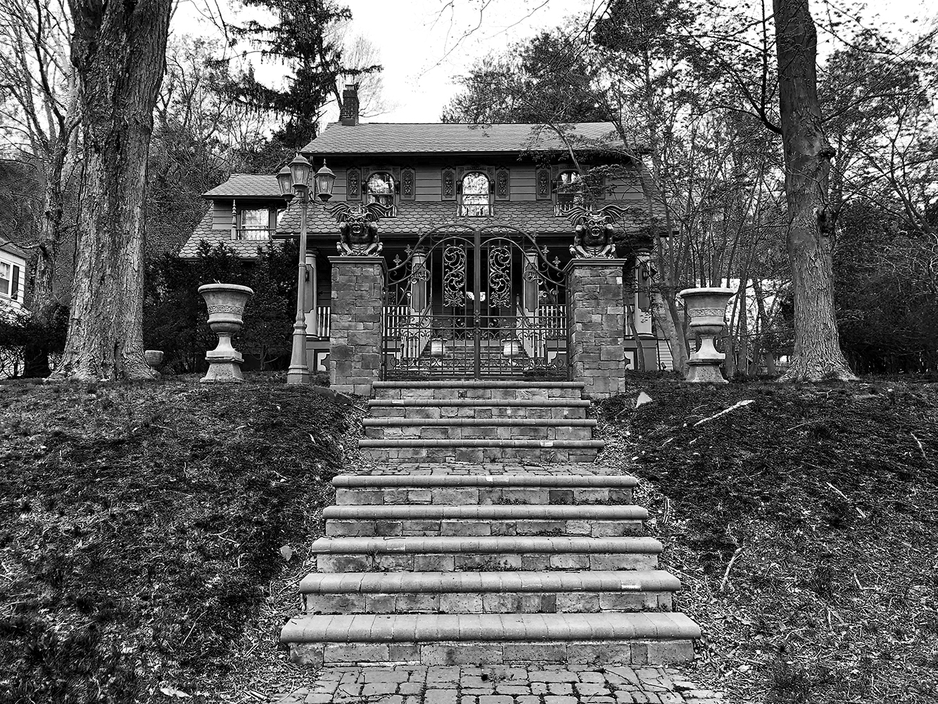 Black and white photo of stone house decorated with gargoyles, pyres and fences Architectural Photography