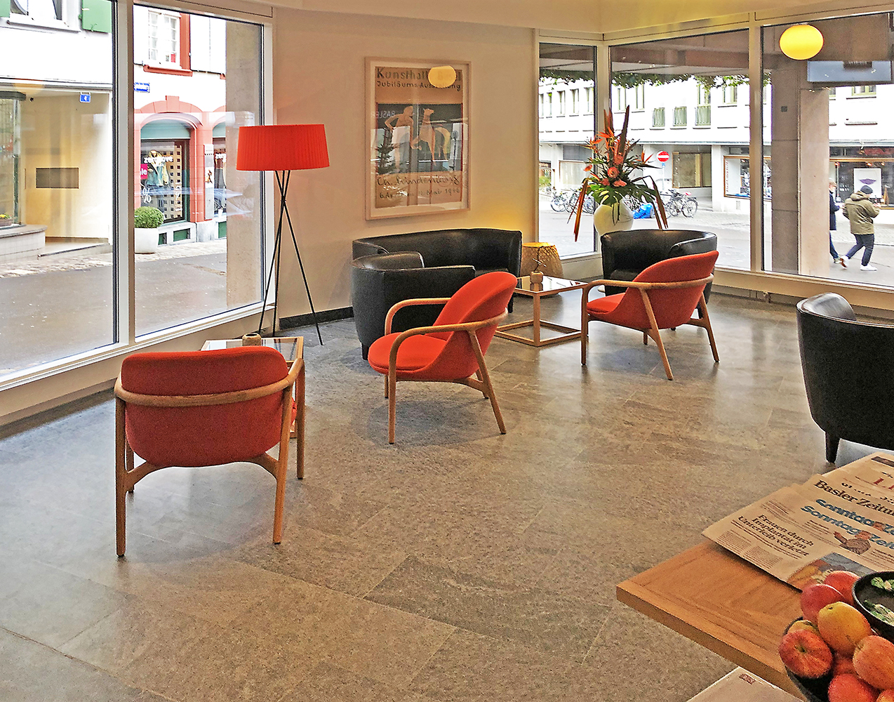 Hotel lobby with red chairs and large windows looking out on the street in Basel Switzerland Architectural Photography