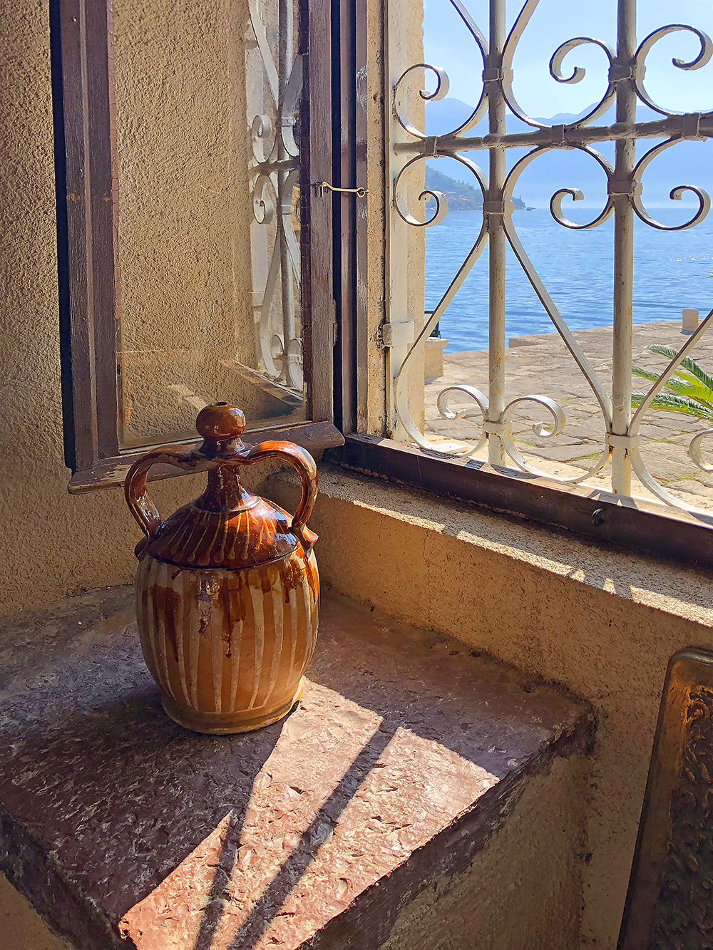 Ancient container on table next to window in church in Montenegro Architectural Photography