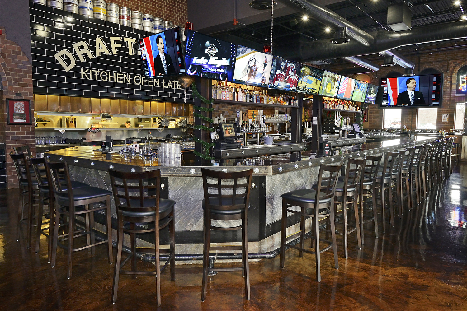 Long bar at Sports Bar with rows of televisions above bar Architectural Photography