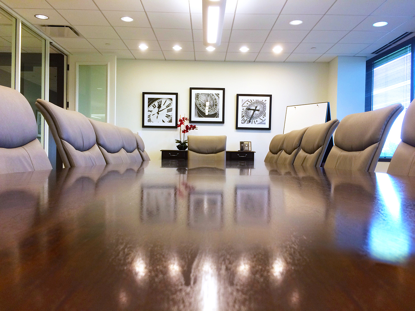 View of board room from table top of chairs, table and back wall with artwork hanging Architectural Photography