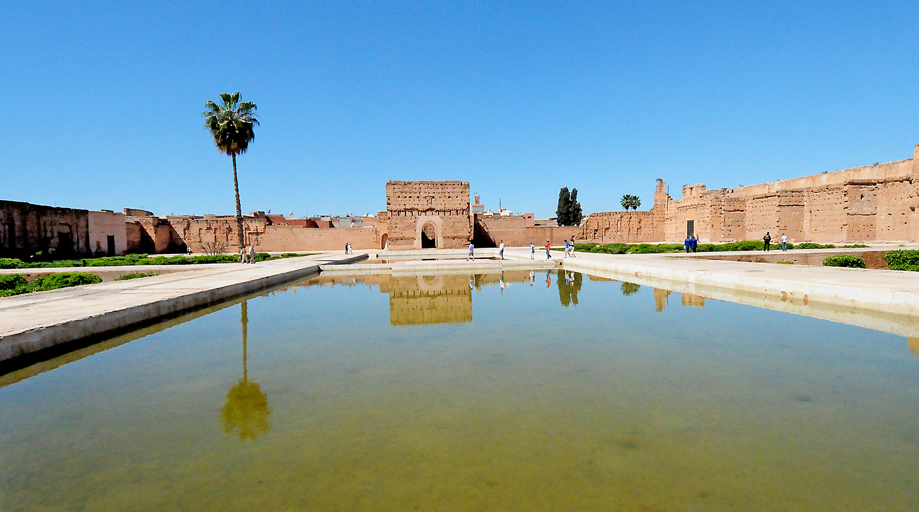 Castle building in Morocco reflecting in pool of water with palm tree on left Architectural Photography