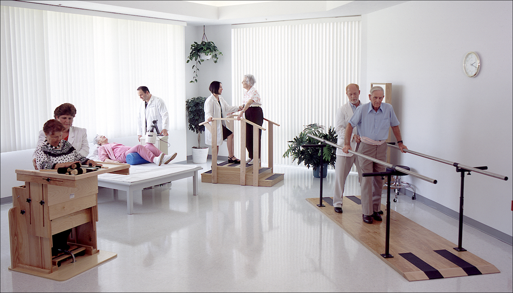 Bright room showing various physical therapy patients working with therapists Corporate Photography