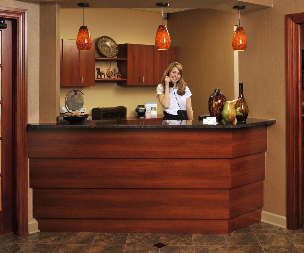 Pretty female receptionist answering telephone at dentist's office with lots of dark wood and hand blown glass lights Corporate Photography Architectural Photography