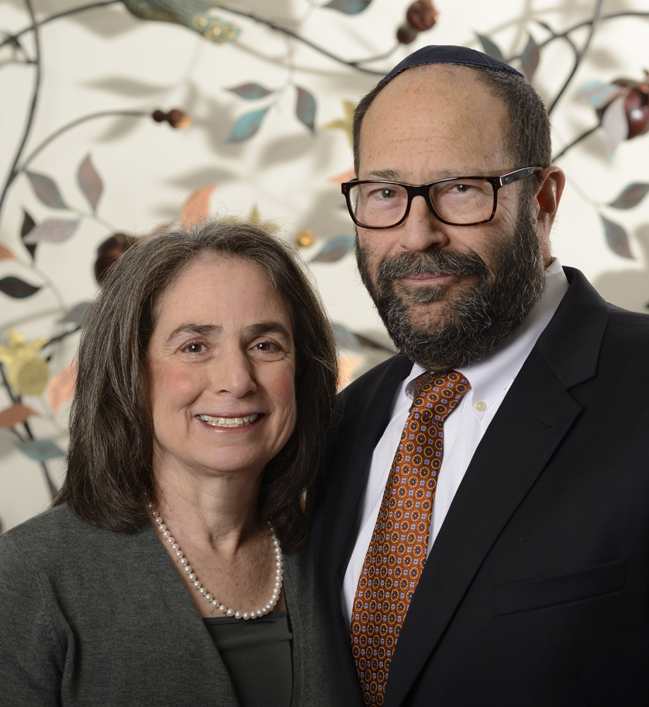 Rabbi and wife portrait in front of decorative artwork