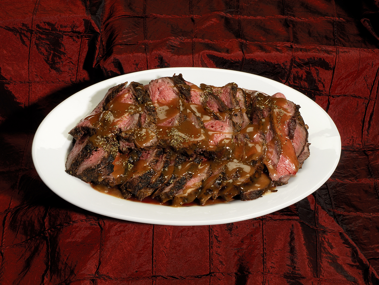 Sliced beef with gravy on white plate