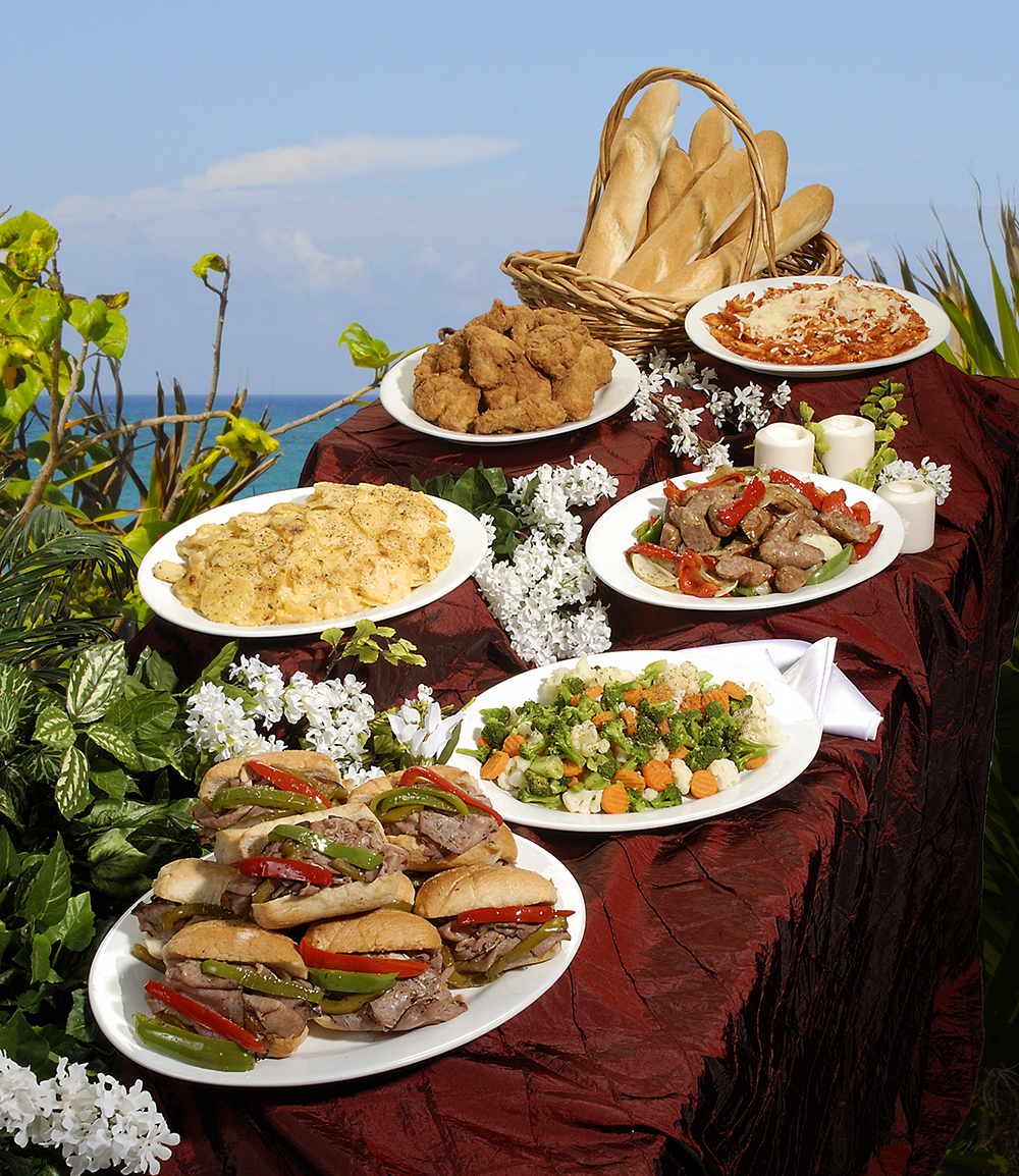 Buffet of food from a caterer, plated and arranged on ret tablecloth with plants and sky in background