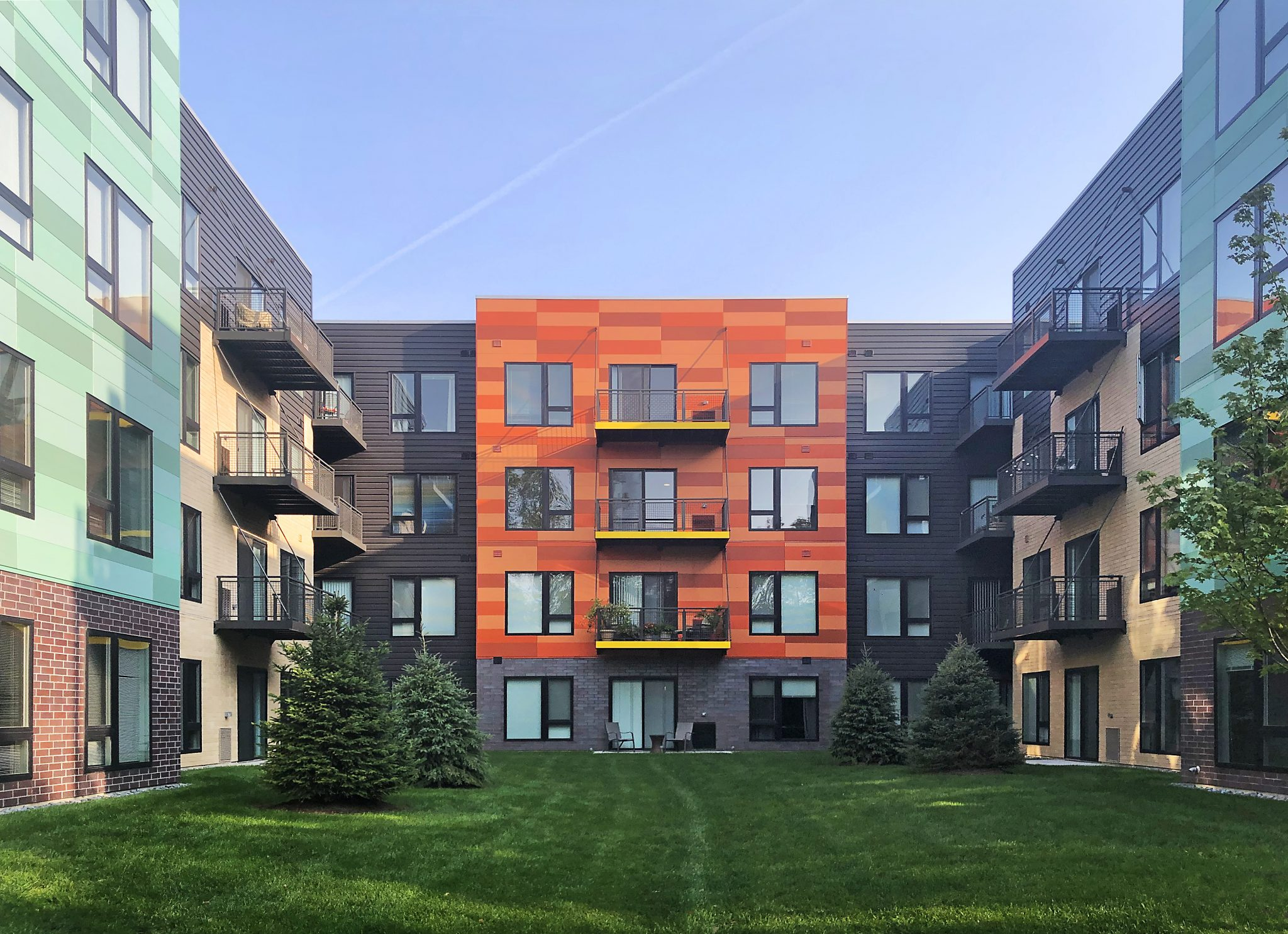 Colorful Residence Courtyard with Orange and teal facade and balconies on a grassy yard