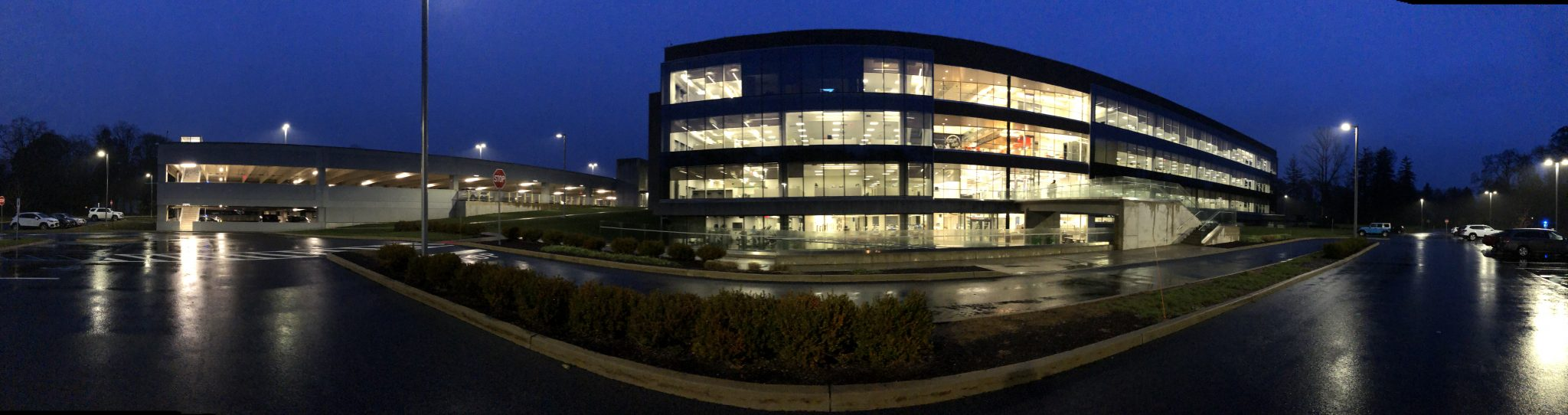 Panorama image of an insurance building at night with indigo sky and wet pavement with windows lit up.