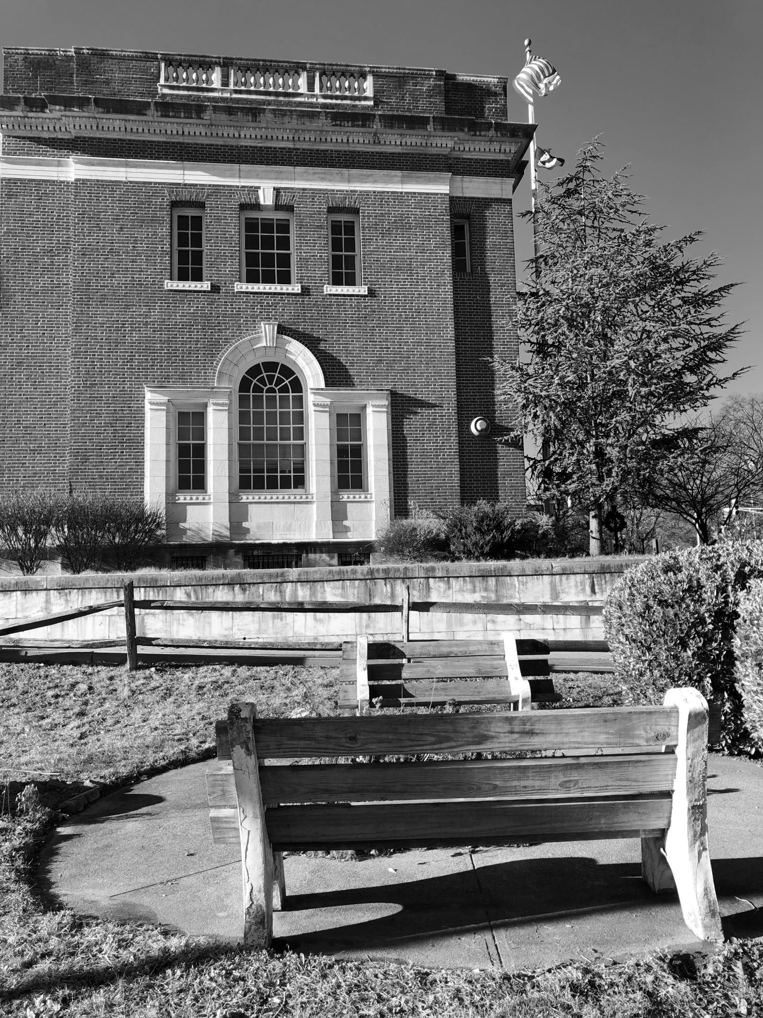 Black and white image of Post Office building in Morristown, NJ with bench outside