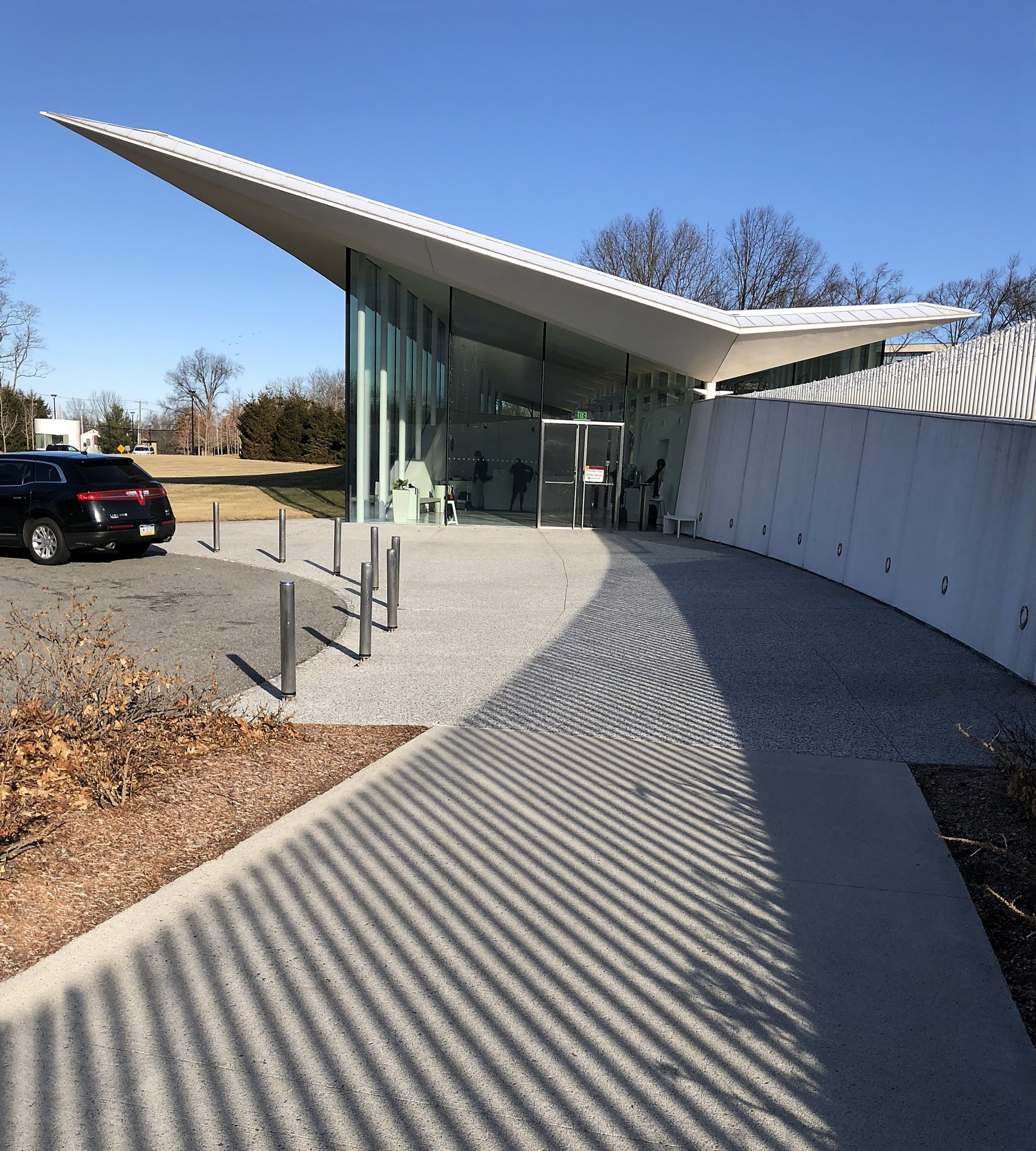 front of Novartis Visitor Center building with soaring white wedge and fencing shadows on sidewalk