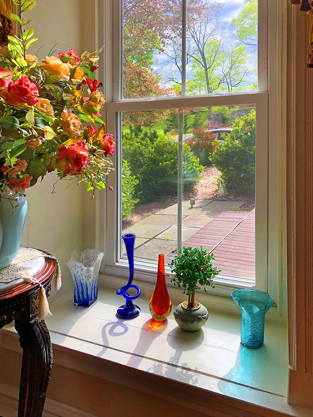 colorful glass sculptures on windowsill with flower bouquet to the left
