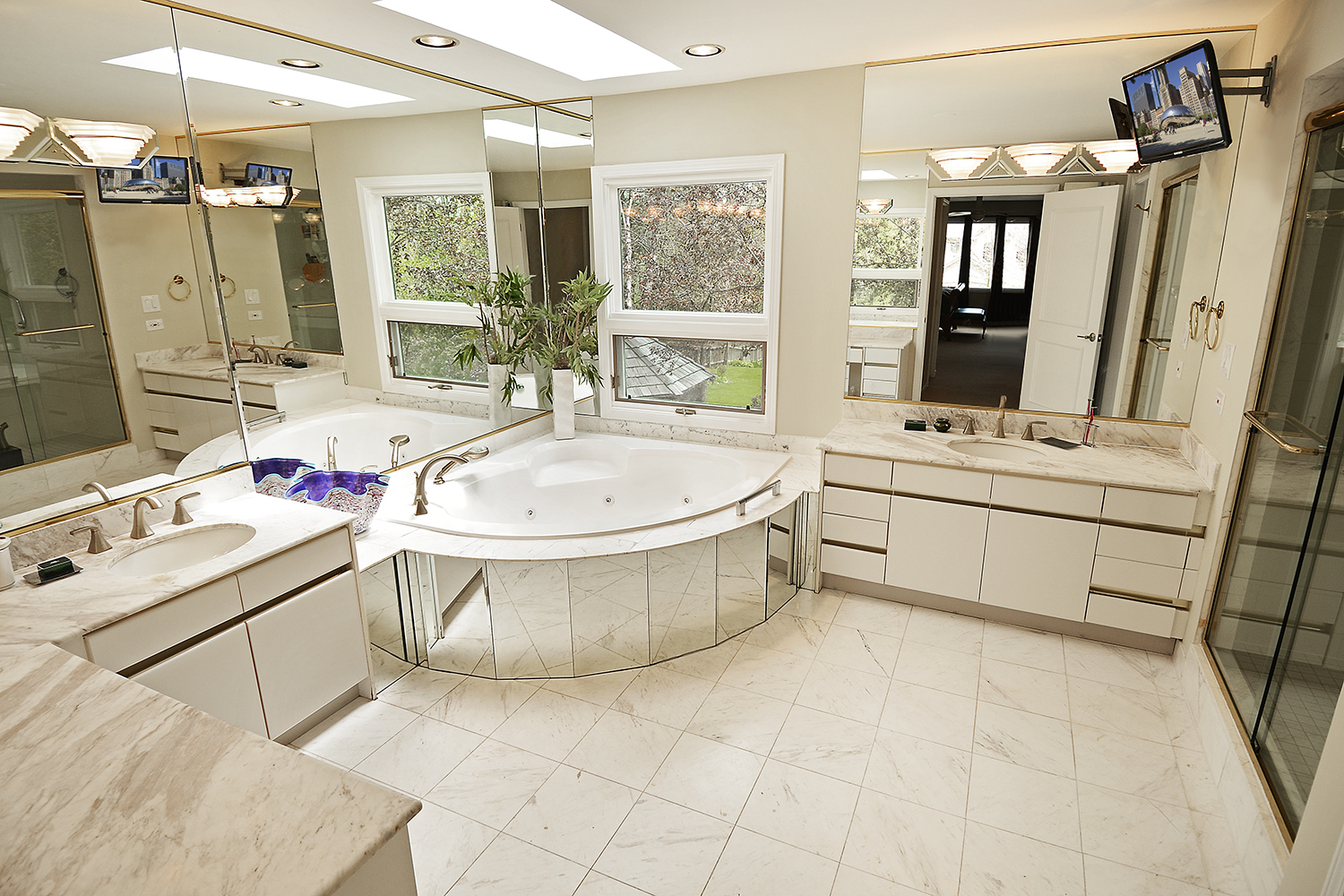 whirlpool bath tub in marble bathroom brightly lit with two TVs mounted on walls