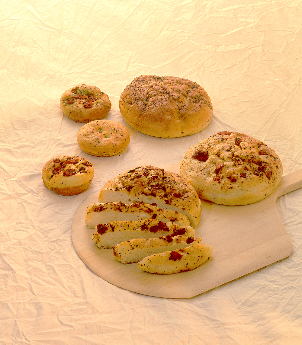 Various loaves of Italian round breads layer out on a canvas backdrop Food Photography