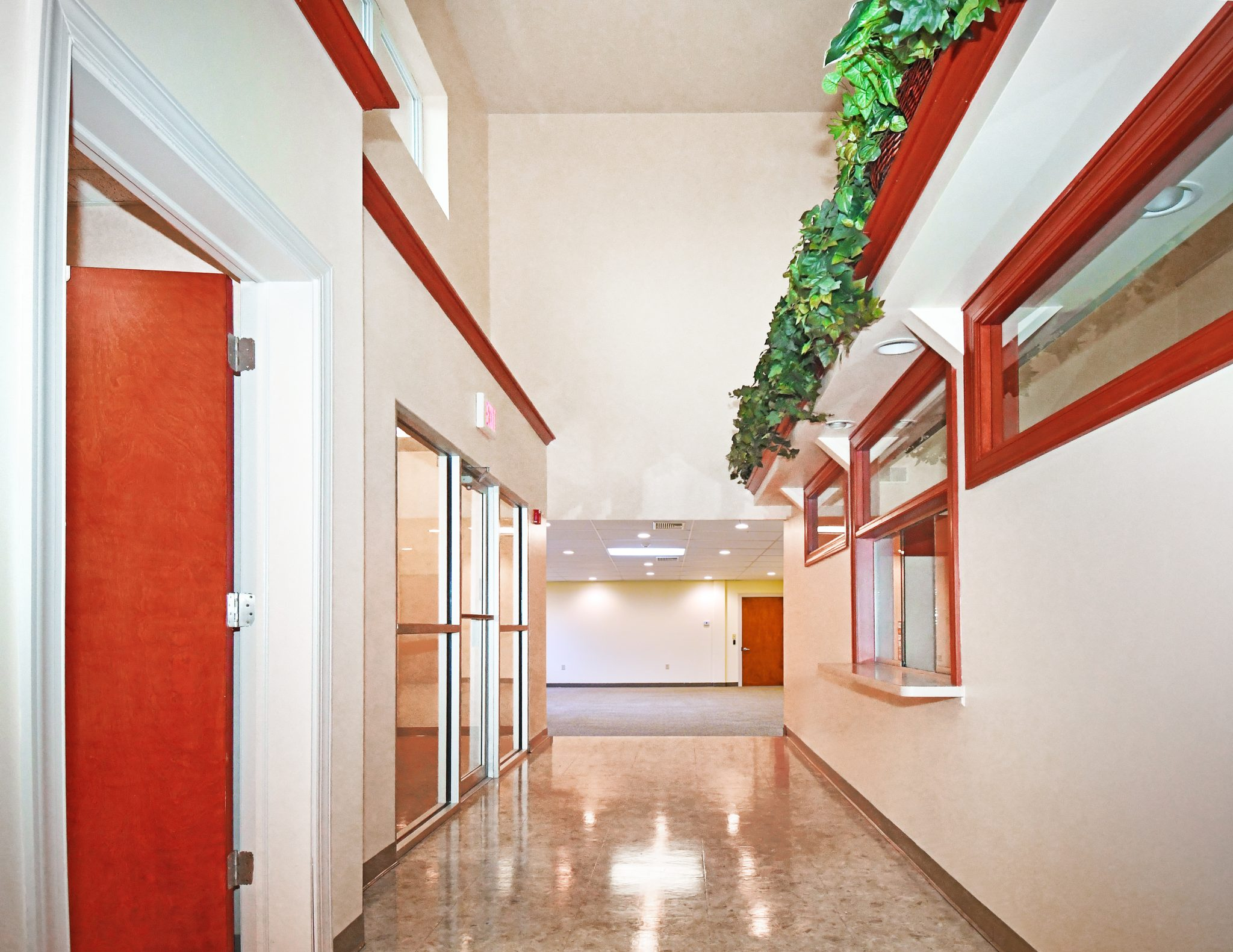 front hallway to medical building with white walls and tile floor and red wood trim with greenery above entrance wall