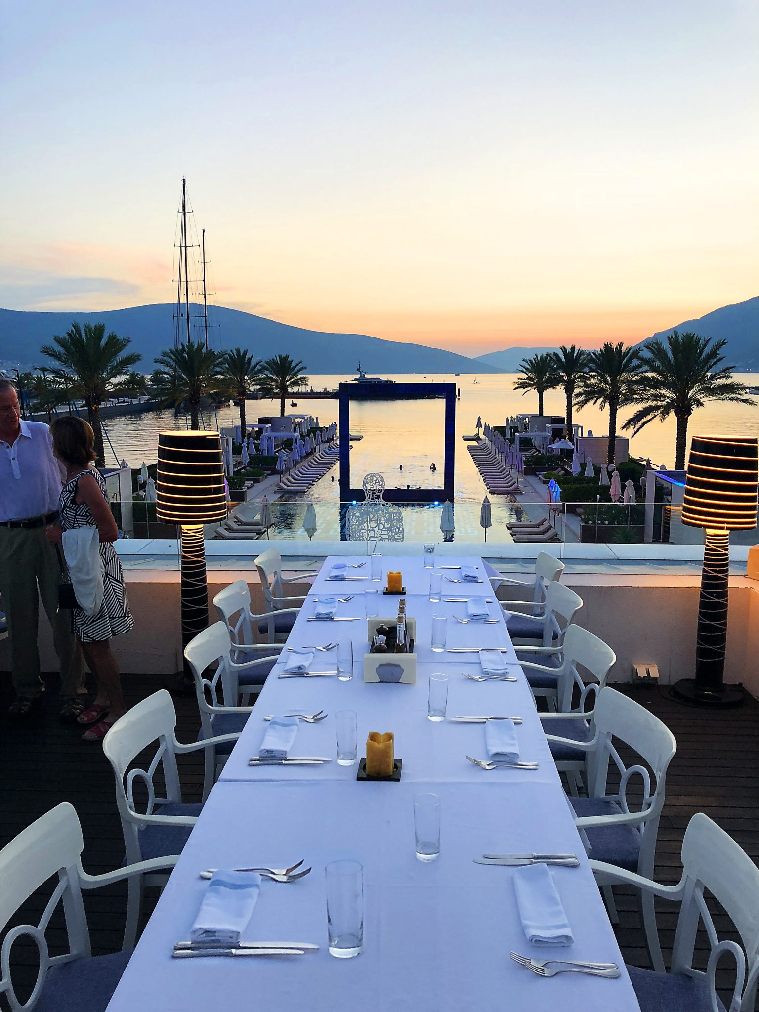 table setting for eight on long table in front of harbor scape with mountains and sunset behind