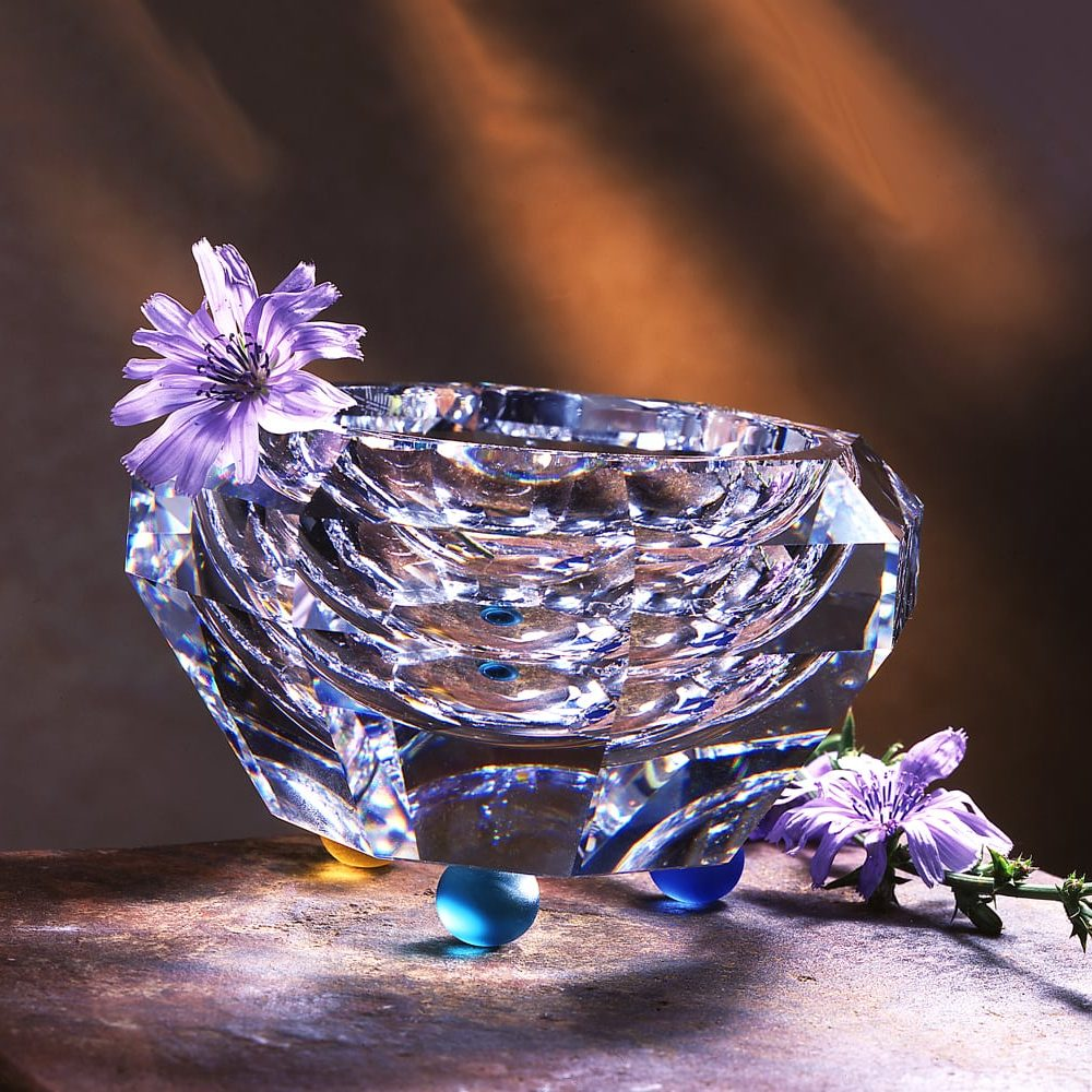 Heavy, angular crystal vase with blue and yellow glass balls for feet and purple flowers as props on textured stone background and orange light streaks behind Product Photography